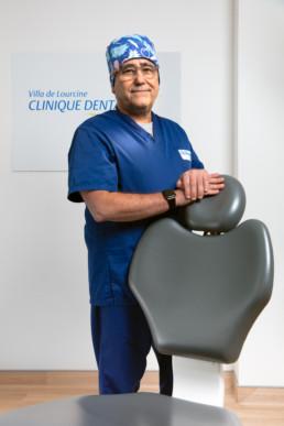un docteur en implantologie dentaire en tenue de travail bleue et calot appuyé sur son fauteuil dentaire