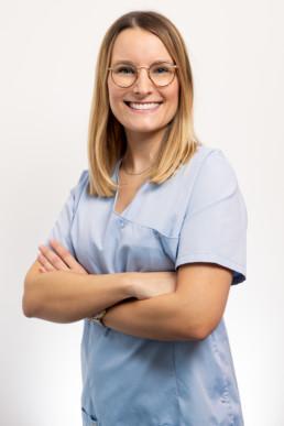 docteur en chirurgie Orale avec une blouse bleu et beau sourire sur fond blanc
